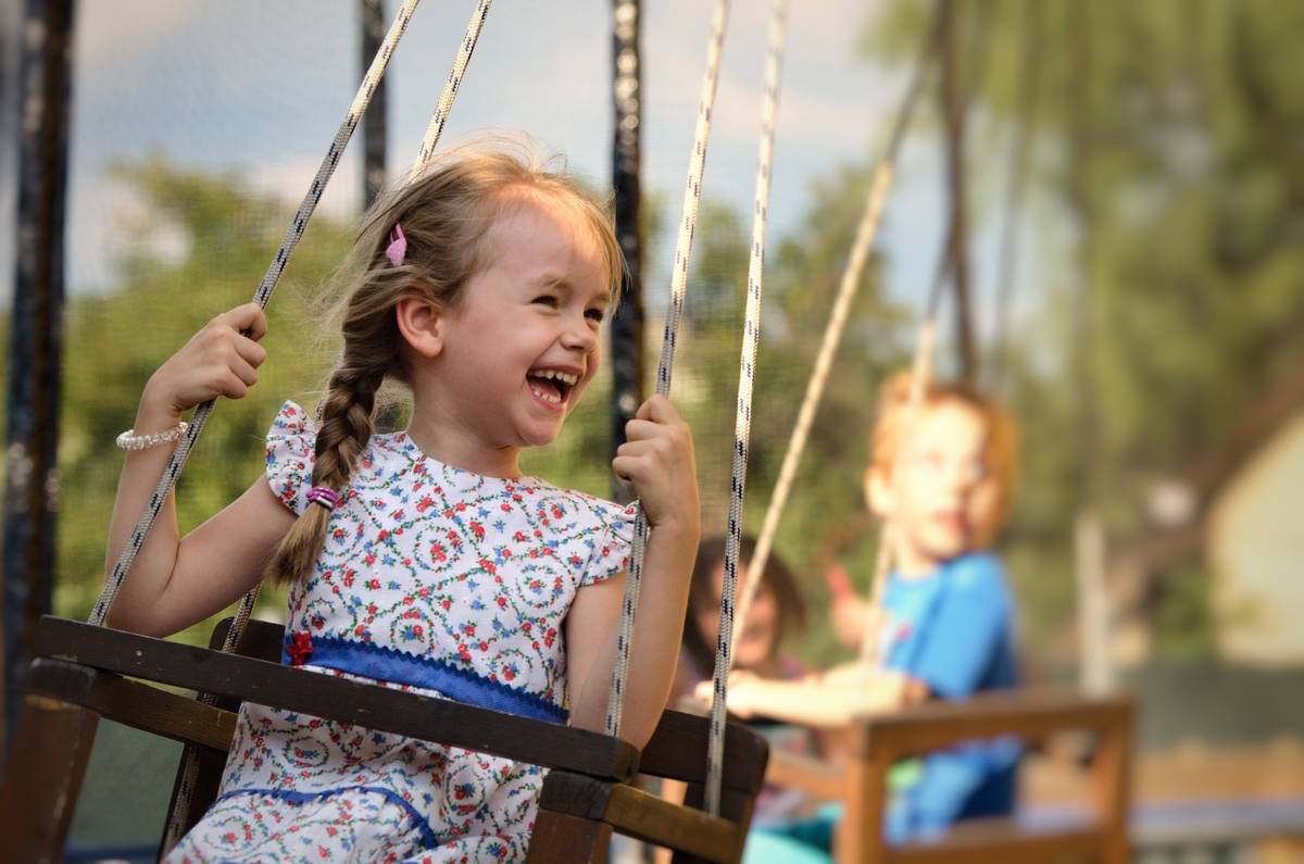 Smiling girl on swing with other children in background
