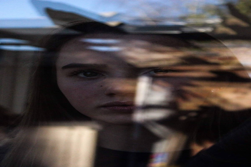Teenage girl seen through glass