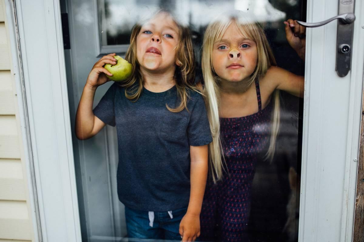 Two girls making faces beside full-lite door
