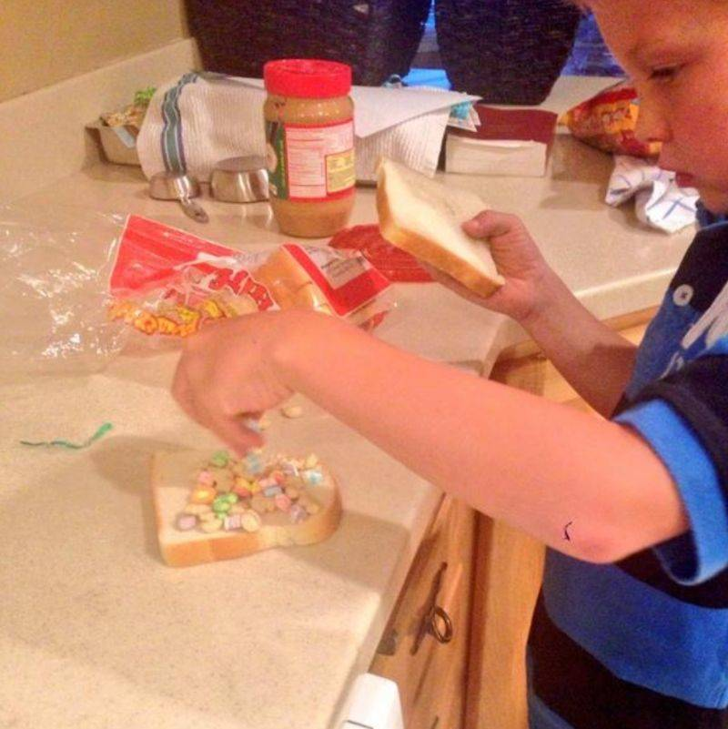 kid making a peanut butter and marshmallow sandwich