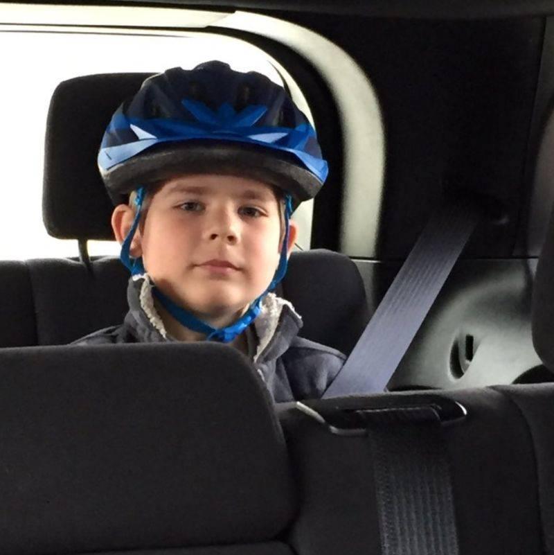 kid wearing a helmet in the car