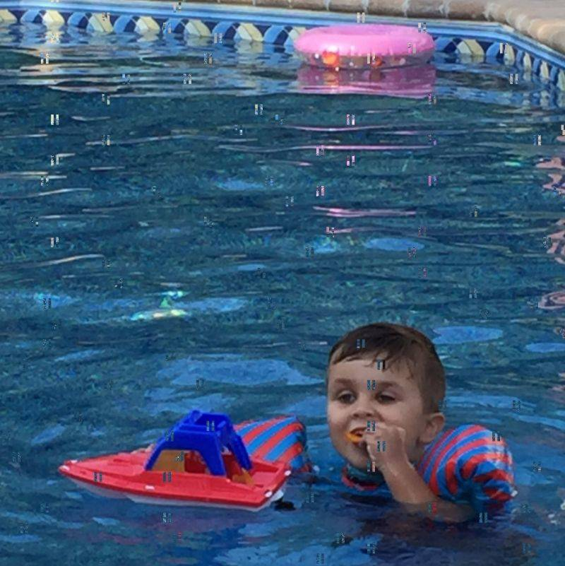 kid eating chips in a boat in the pool