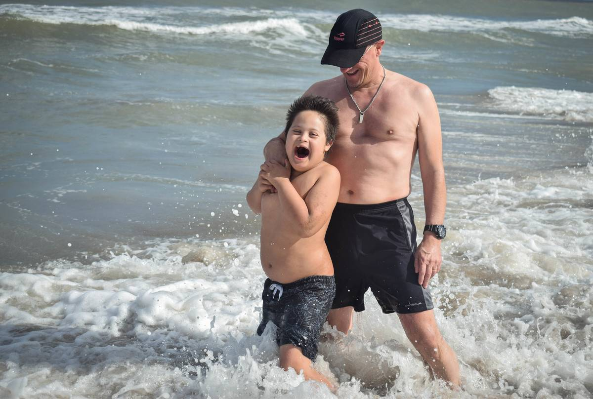 man hugs boy in water on beach