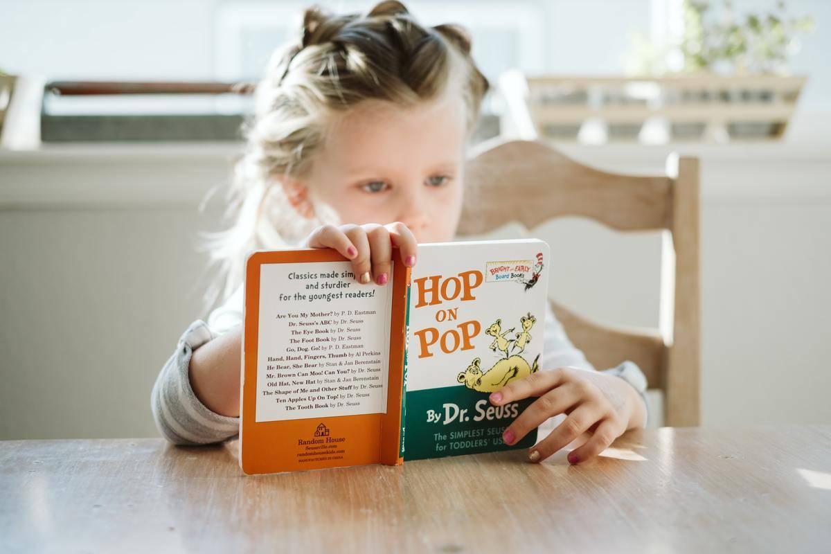 a little girl reading a Dr Seuss book