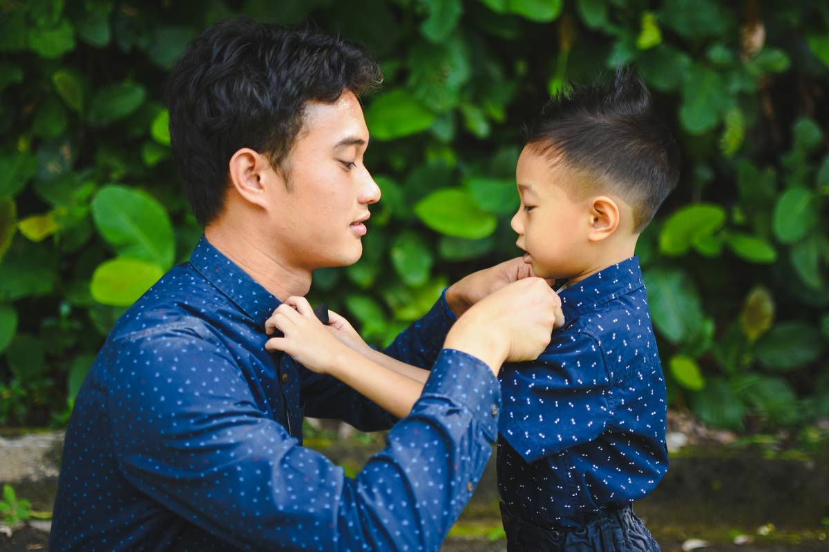 Man in blue long sleeve shirt helping young boy in similar shirt with collar