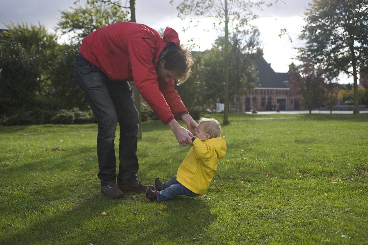 Man in red jacket holding boy in yellow jacket on grass field