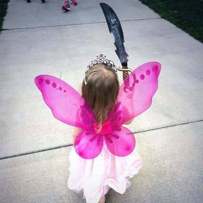 a little girl dressed up as a fairy with a sword