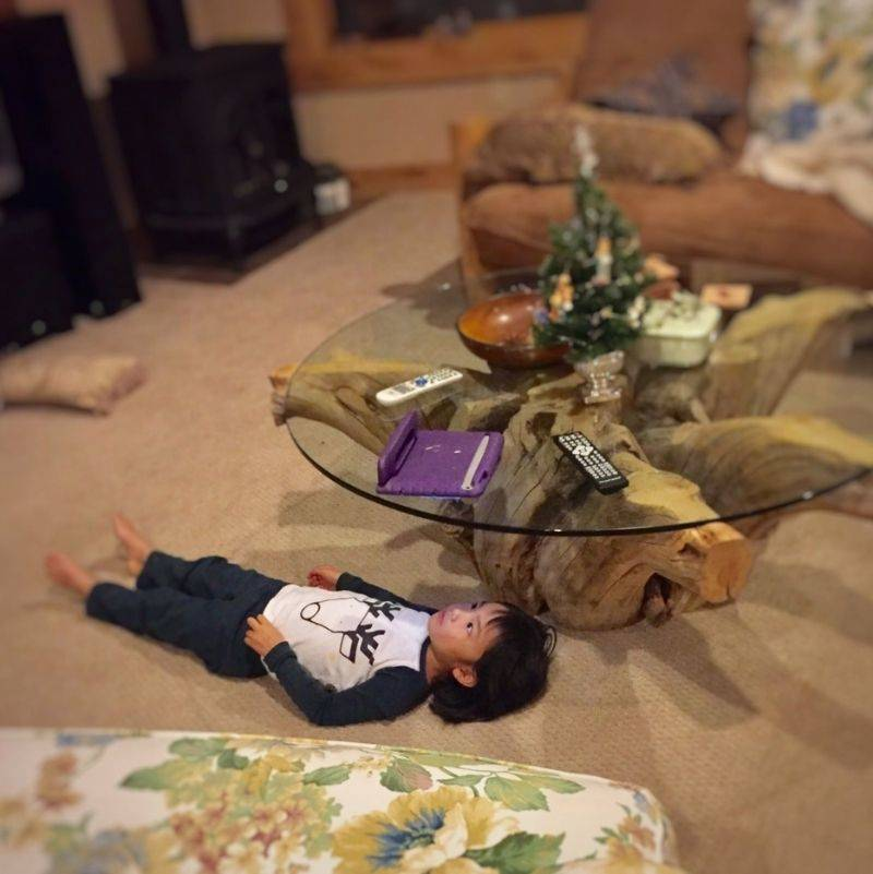 a little kid watching iPad on a glass table