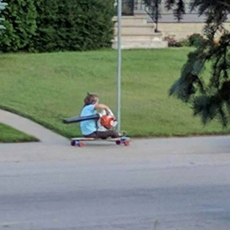 a kid using a leaf blower to move them on their skateboard