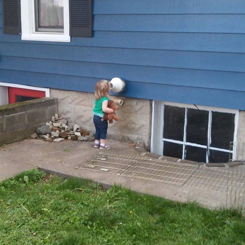 kid talking to a vent in the yard