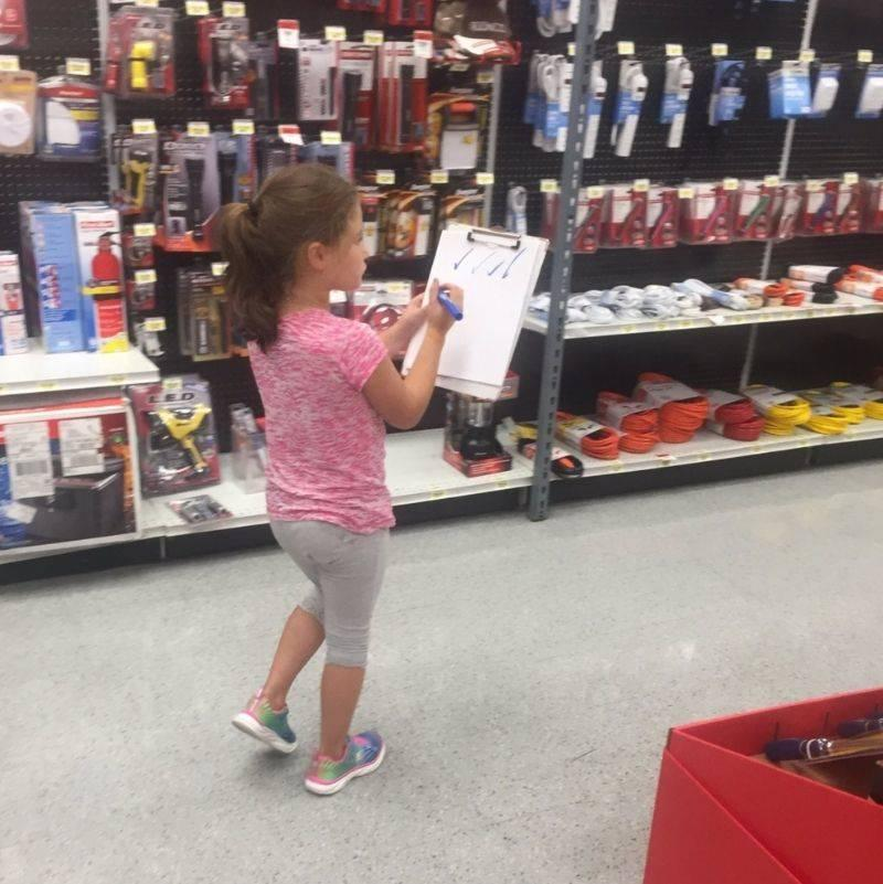 little girl walks around a store checking things off