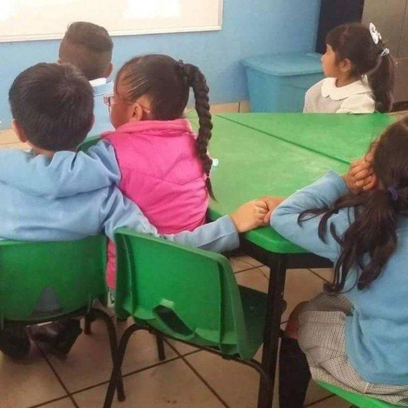 little boy holding hands with two different girls