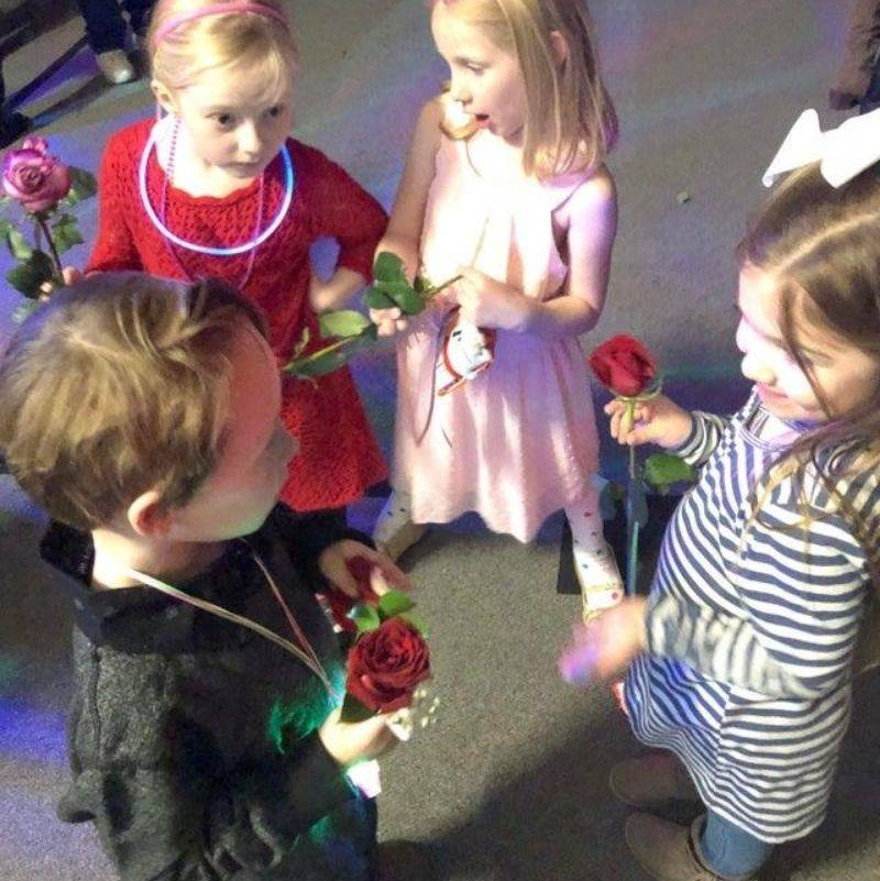 a little boy handing out roses to a bunch of girls