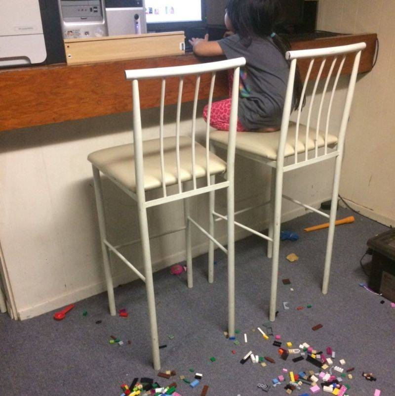 little girl put Lego all around her chair so no one comes near her