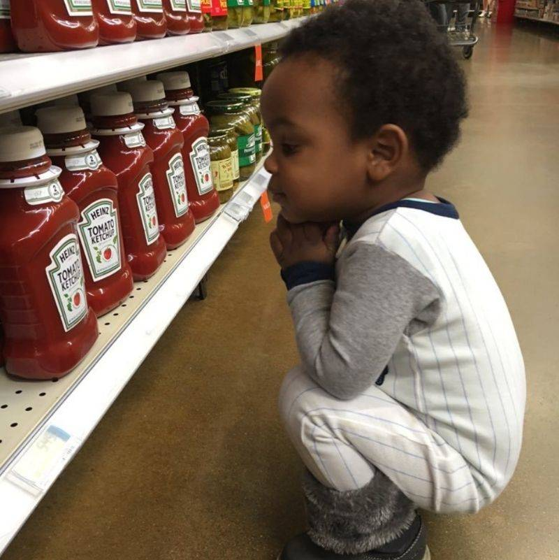 a little kid looking lovingly at ketchup