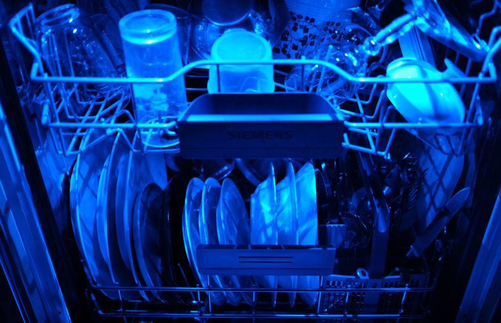 13 April 2020, North Rhine-Westphalia, Cologne: Washed dishes are in an open dishwasher with blue lighting. Photo: Oliver Berg/dpa