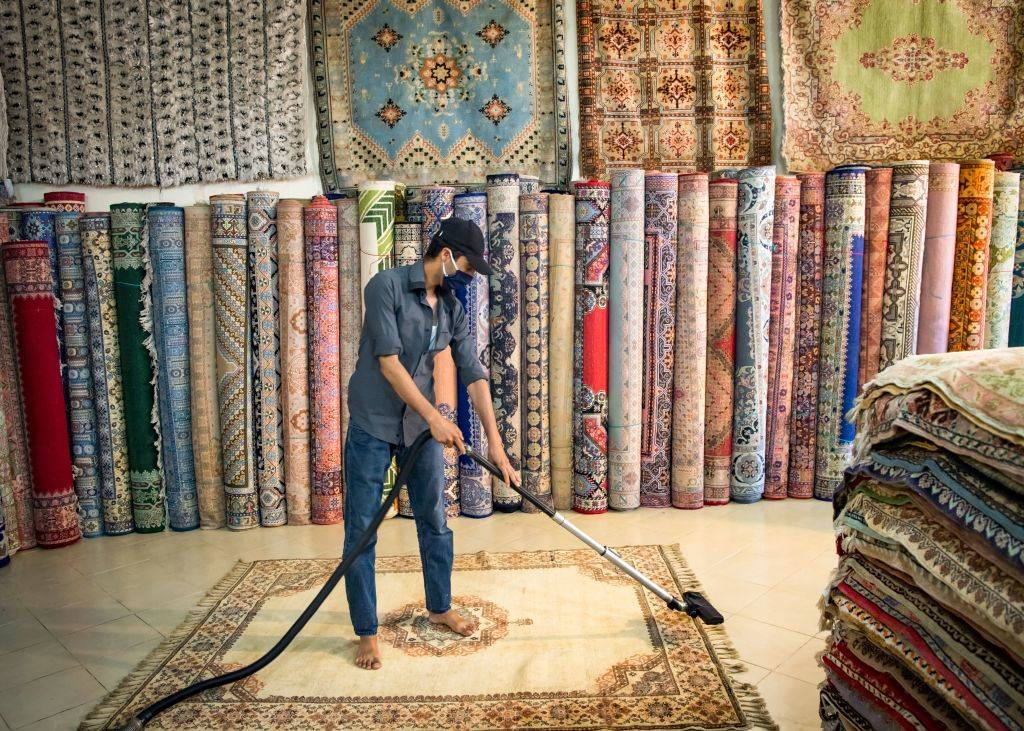 A Moroccan rug dealer cleans a carpet at a shop in the city of Sale, north of the capital Rabat, on June 3, 2020, during the novel coronavirus pandemic. - Artisans in Morocco have been starved of income for almost three months because of the COVID-19 pandemic. The crafts industry represents some seven percent of GDP, with an export turnover last year of nearly 1 billion dirhams ($100 million).