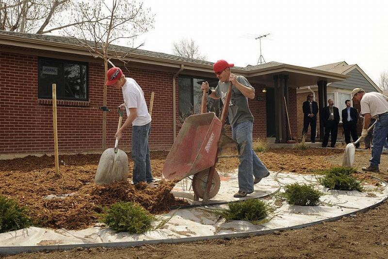 A landscaping crew from Prairie Snow Enterprises out of Keenesburg, CO, place mulch around new plants in front of a new HUD rehab home in Aurora