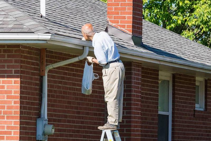 Seniors in Canada: Senior man cleaning a rain gutter on a ladder. Clearing autumn gutter blocked with leaves by hand.