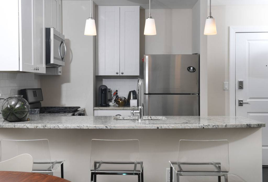WASHINGTON, DC - NOVEMBER 12: Laura Kiker's kitchen has granite counter tops, stainless steel appliances and pendant lighting November 12, 2017 in Washington, DC. Kiker's building previously was a section of Specialty Hospital Capitol Hill. (