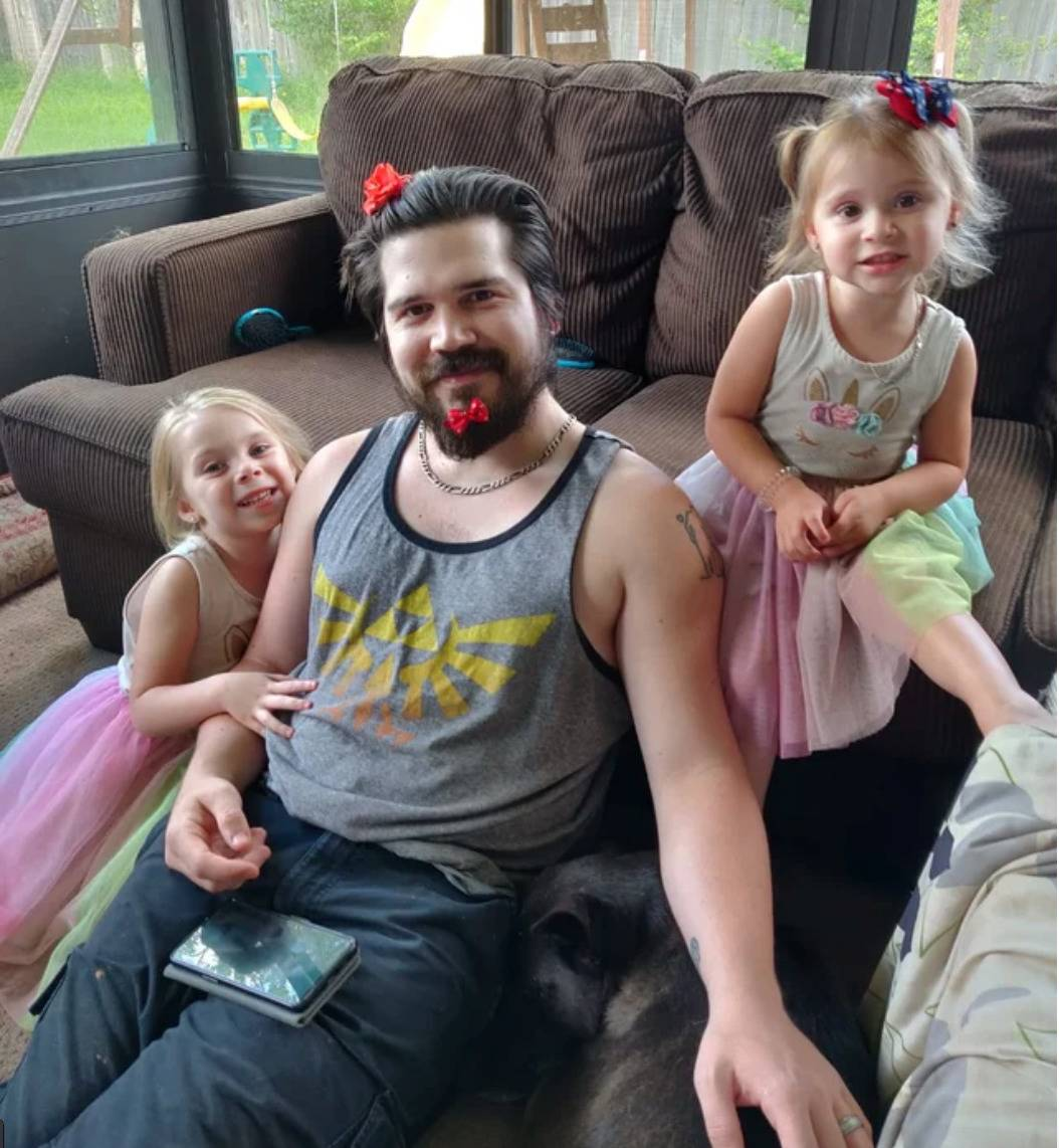 dad with bows and hair clips in hair and beard sitting with two daughters