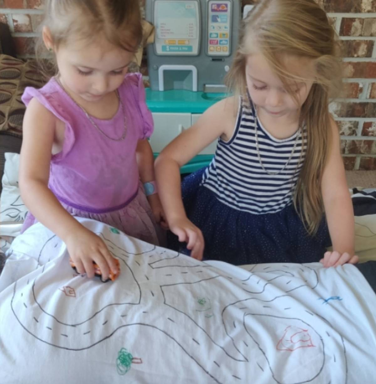 girls play with cars on track drawn on back of dad's shirt