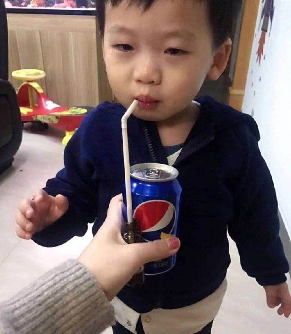 woman holds pepsi with straw behind it in medicine up for son who's drinking it