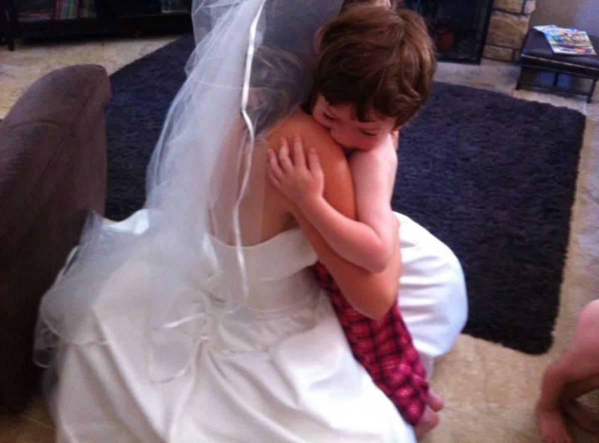 boy hugging woman in wedding dress