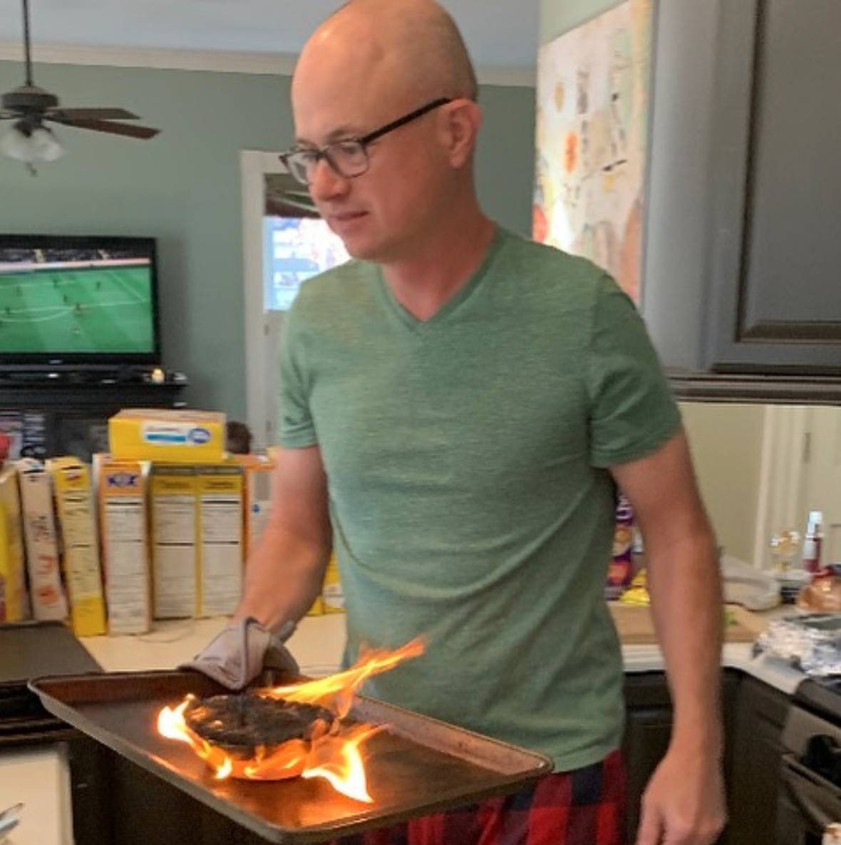 man holding baking tray with chicken pot pie on fire