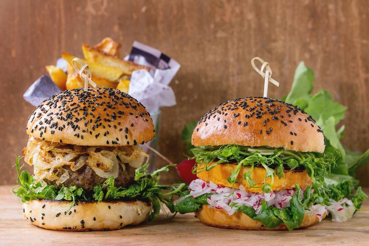Homemade traditional and veggie burgers with beef, fried onion, sweet potato, radish and pea sprouts, served over wooden textured background. Healthy vs unhealthy concept food.