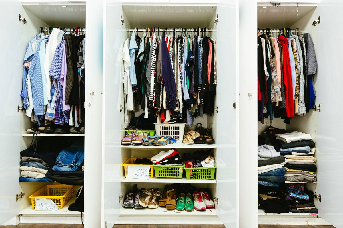 clothes and shoes are seen inside a closet