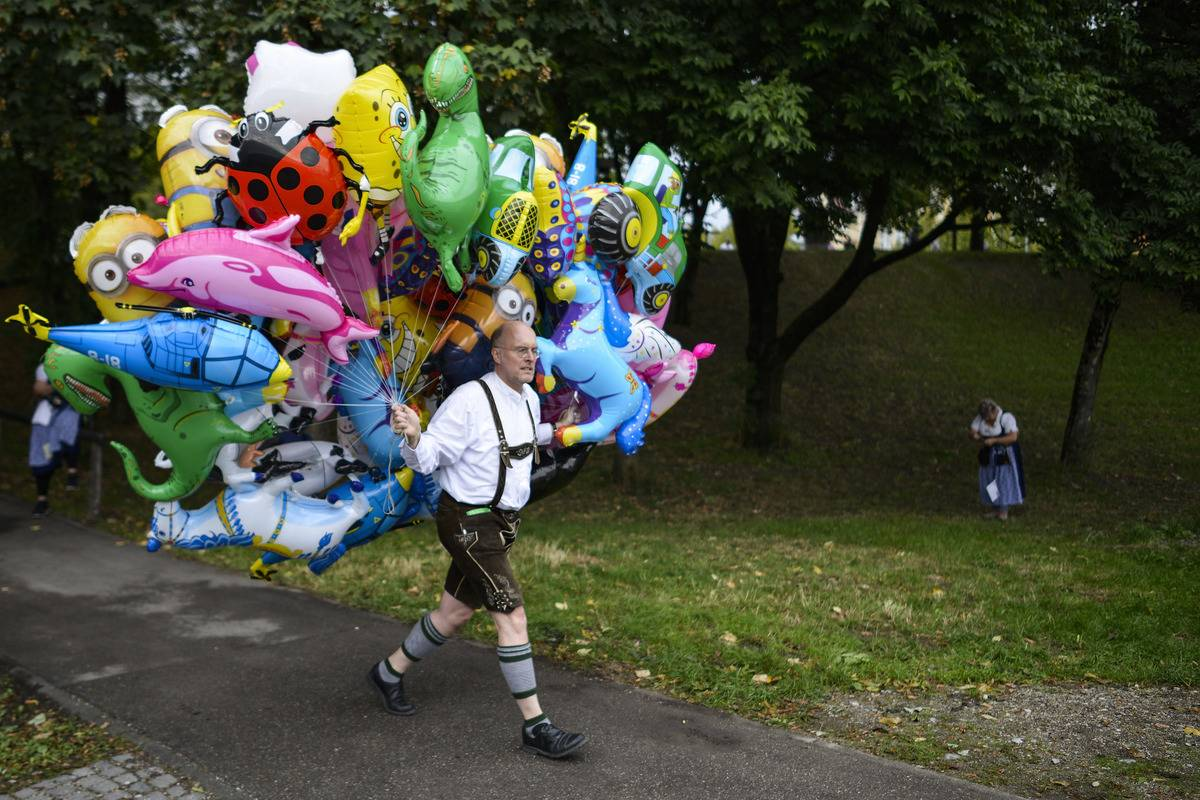 A baloon-vendor in bavarian folk attire carries a bunch of helium baloons