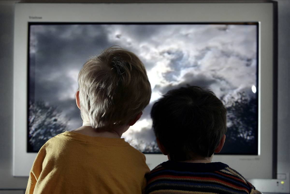 two young child watch television at home