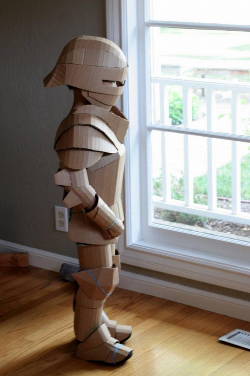kid wearing armor made of cardboard in house