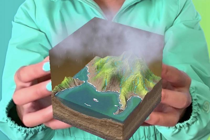 child holds virtual merge cube