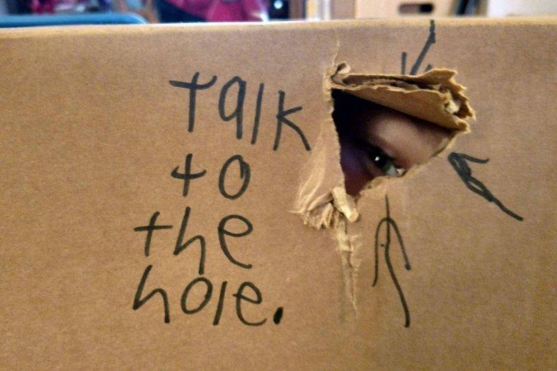 kid made a hole in a cardboard box that says,