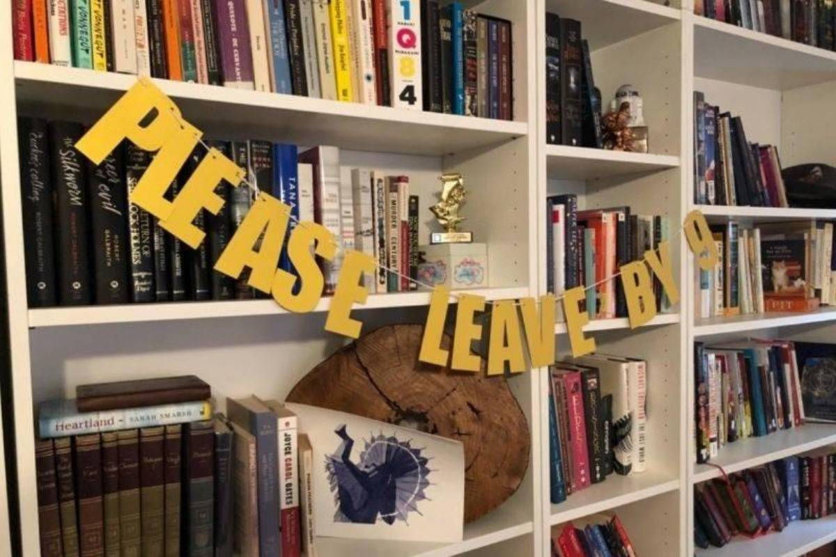'please leave by 9' banner on bookshelf