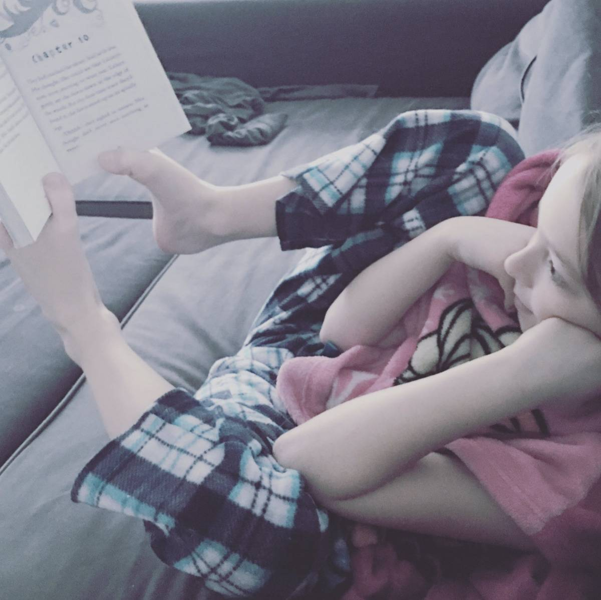 kid reading with her toes holding the book