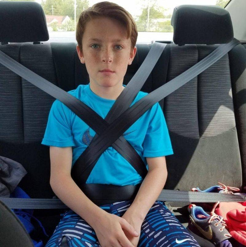 kid putting on all the seat belts in the car