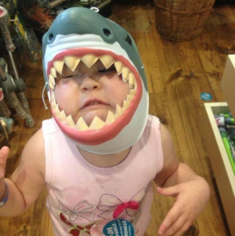 a kid wearing a shark mask