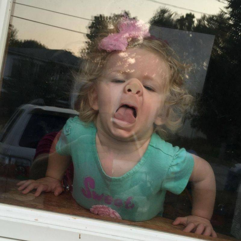 kid making a face at the window