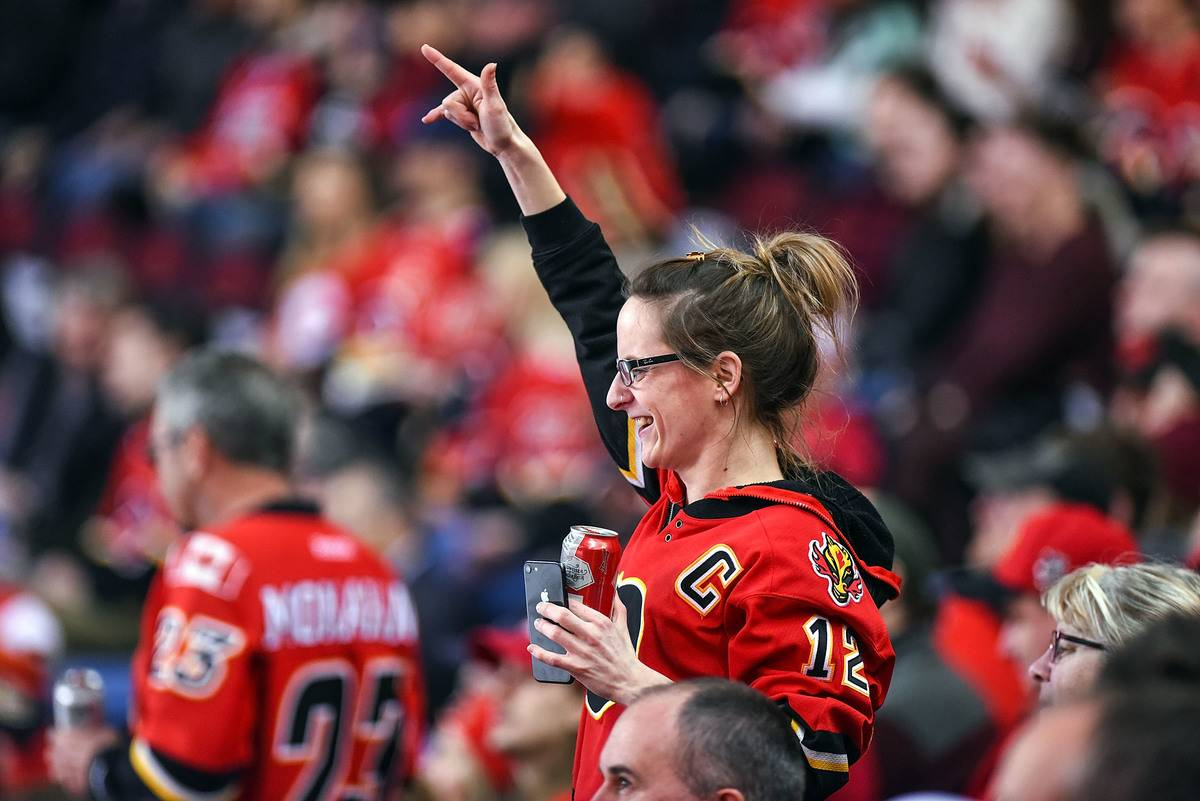 A Calgary Flames fan celebrates a goal by her team during the third period of an NHL game