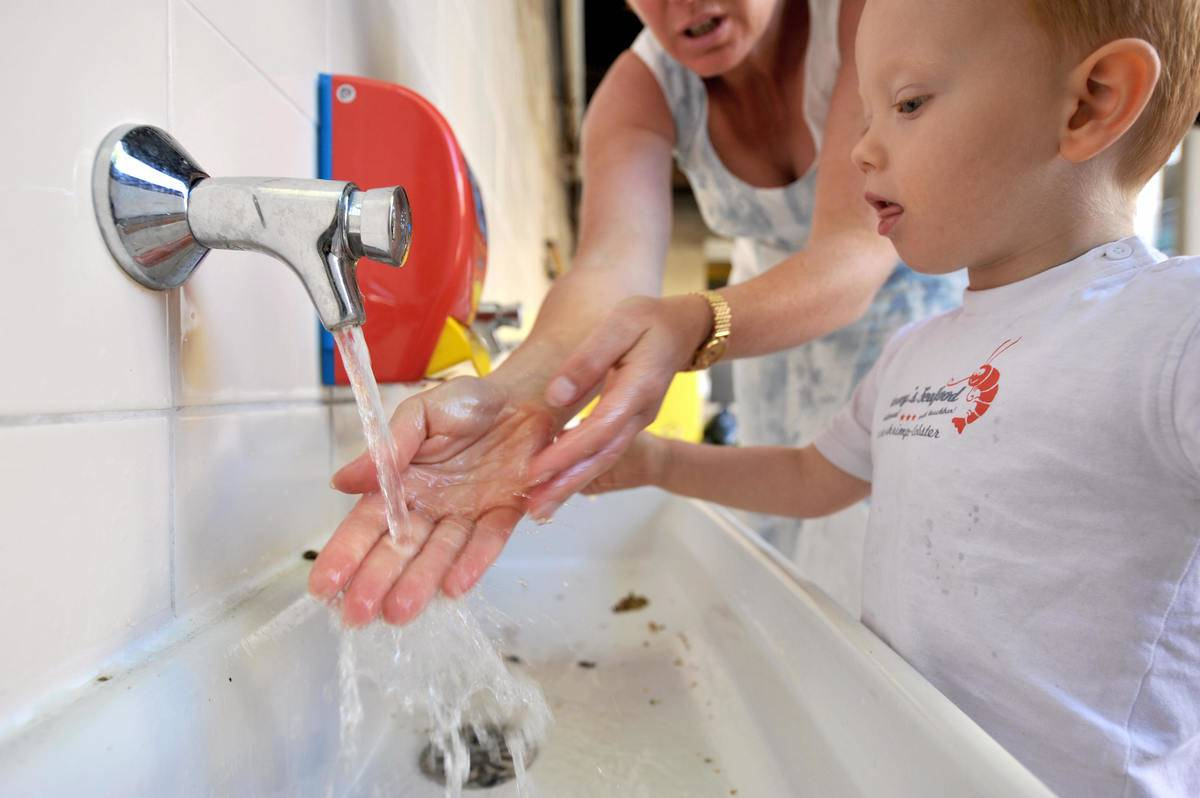 A woman shows a child how to wash his hands with an antibacterial hand gel