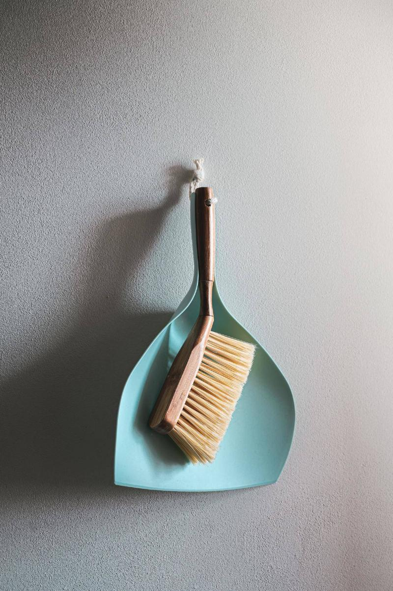 Dust pan and brush hanging on wall together