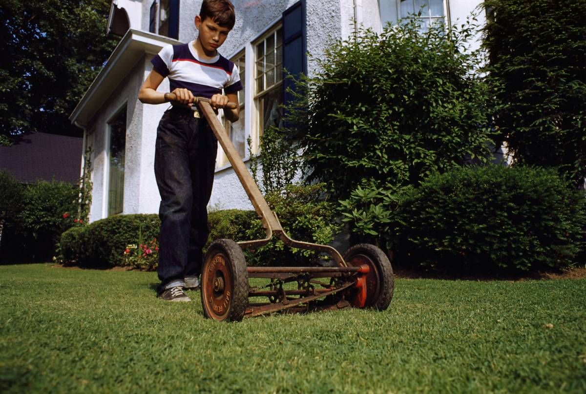 boy mowing the lawn