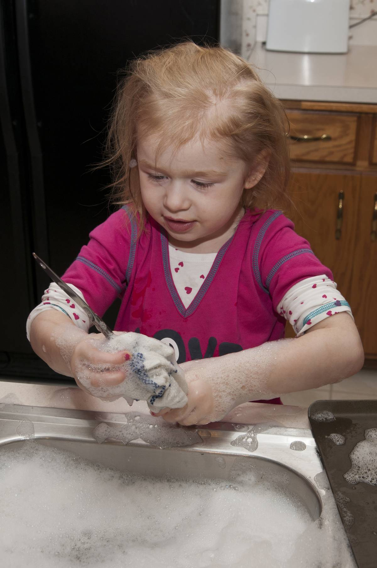 Girl helping with chores by doing dishes