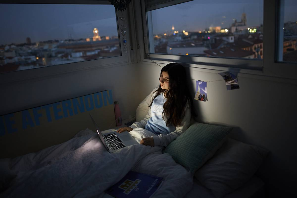 a teenage girl watches a series using laptop on the bed in her room