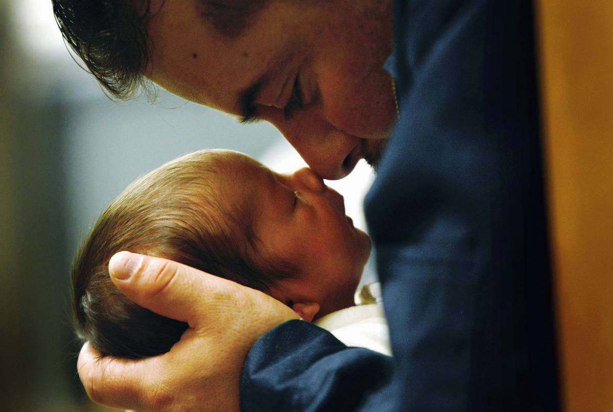 man touches noses with newborn son