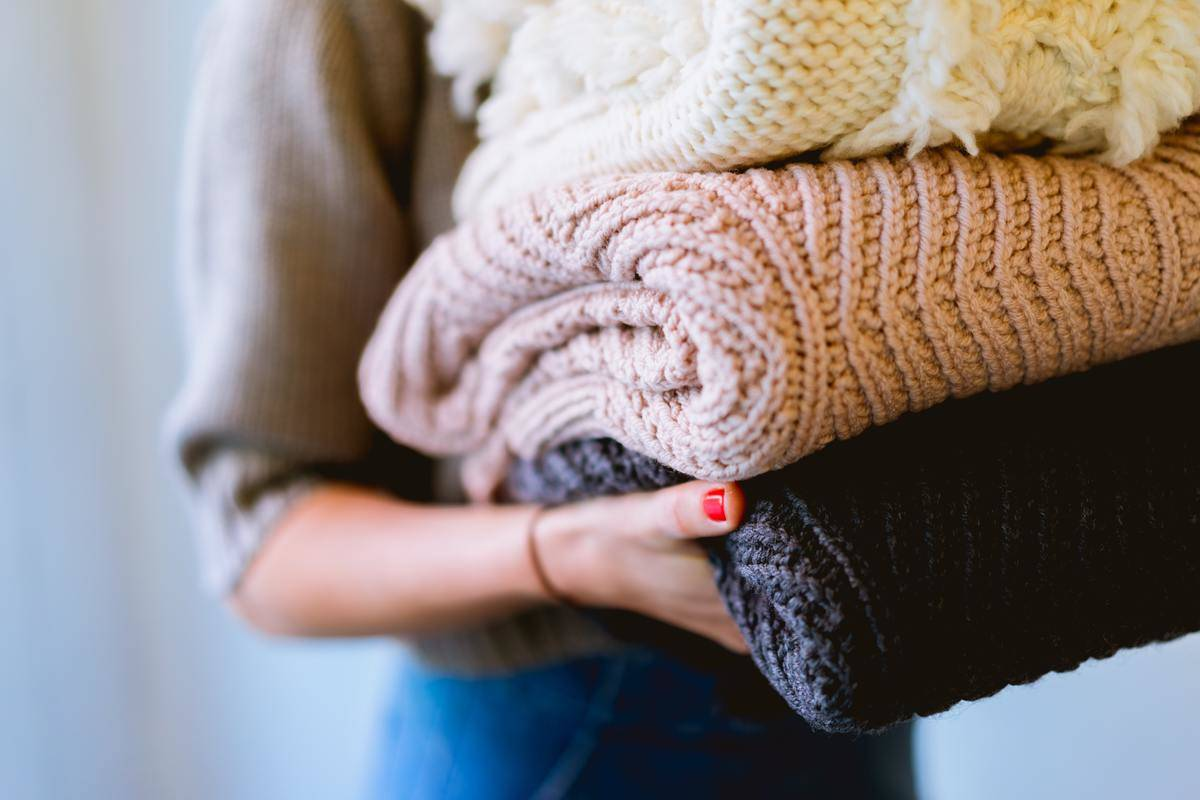 person carrying stack of folded sweaters