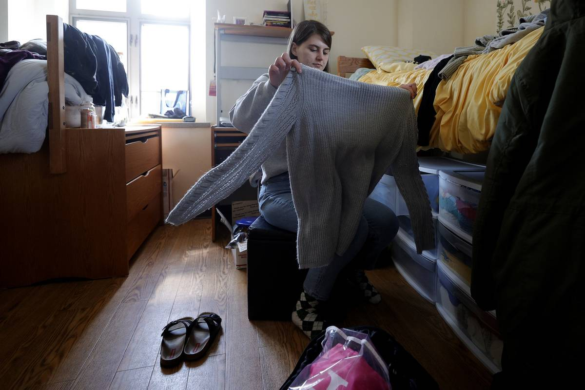 student in dorm folds clothes